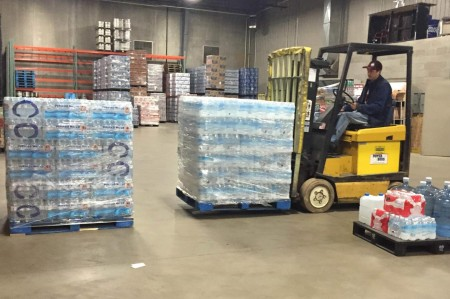Atlas Sales Inc. employee Nate Hisler transfers cases of water donated by Atlas Sales, Territorial Brewing Co. and Schweitzer Construction for Flint in response to the ongoing water crisis.